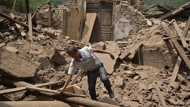 A man checks a destroyed house following an earthquake which hit Luozehe town in Yiliang county in southwest China's Yunnan province.