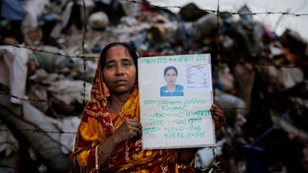 Henna Begum holds a picture of her missing daughter, Akhi Akhter, who was a garment worker, following the April collapse of the Rana Plaza building in Bangladesh.