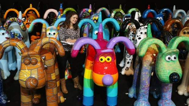 An organizer of Gromit Unleashed walks among the giant Gromit sculptures decorated by artists and celebrities before Thursday's auction, which raised raised $3.84M for Bristol's children's hospital.