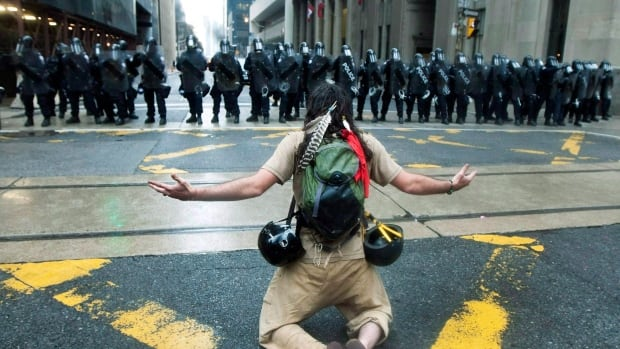 A protester reacts to the riot police while marching along the streets of downtown Toronto during the G20 Summit on Saturday, June 26, 2010.