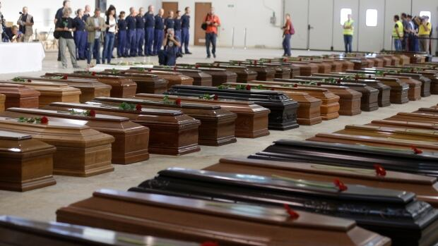 Coffins of dead migrants are on display at Lampedusa's airport. Just 155 people survived the tragedy.