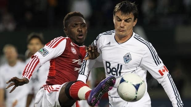 Portland Timbers' Kalif Alhassan, left and Vancouver Whitecaps'Alain Rochat fight for the ball in a game on May 26 in Portland.
