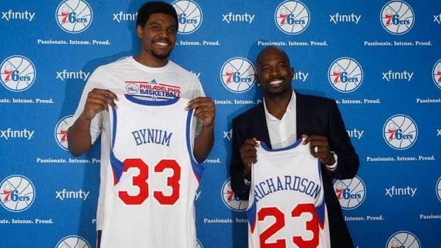 Philadelphia 76ers players, Andrew Bynum, left, and Jason Richardson, pose with their new jerseys after being introduced at a news conference in Philadelphia on Wednesday.