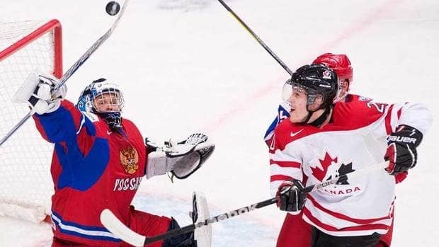 Team Canada forward Brett Ritchie, right, battles for the loose puck with Russia goalie Andrei Makarov, left, during first period in Ufa, Russia on Monday.