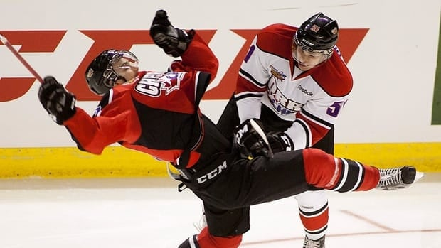 Team Cherry's Danill Zharkov, left, gets checked by Team Orr's Derrick Pouliot during the first period at the CHL Top Prospects Game in Kelowna, B.C. on Wednesday.