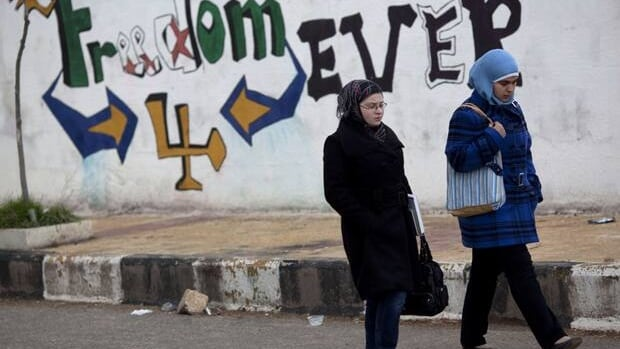 Women walk past graffiti that reads Freedom for Ever on the outskirts of Idlib, north Syria, Thursday.