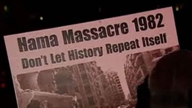 A protester in Ottawa holds a placard at a candlelight vigil for Syria highlighting the current bloodshed and 1982's Hama massacre.
