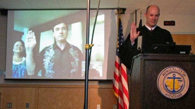 Anchorage Mayor Dan Sullivan, seen on screen, with his wife, Lynette, takes the oath of office for his second term via a video link from Honolulu, as it is administered by Judge Brian Clark.