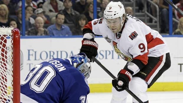 Ottawa Senators left wing Milan Michalek, right, tries to get a shot past Lightning goalie Dwayne Roloson in first-period action on Tuesday night.