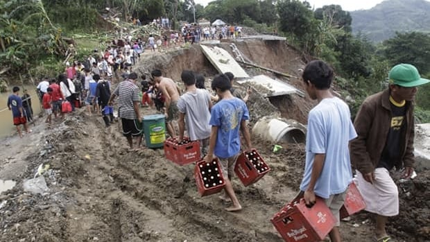 People carry their merchandise on a muddy part of the collapsed road in suburban Antipolo City, east of Manila, on Thursday.