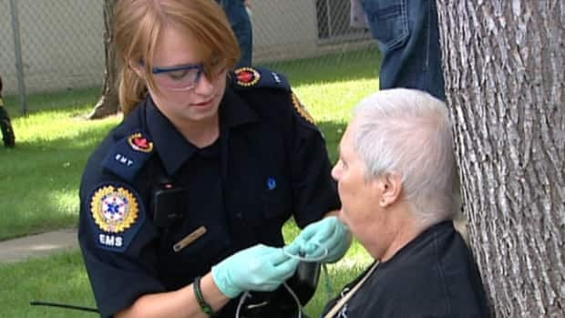 An EMT cares for a resident who was forced to leave the Canora Gardens seniors residence after a fire on Tuesday afternoon.