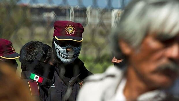 A state police officer wearing a death's-head face mask stands behind the fence as relatives of inmates wait for news after a prison riot at Apodaca correctional state facility on the outskirts of Monterrey, Mexico, Sunday.