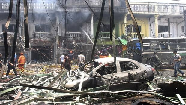 Thai fire fighters and soldiers walk at the site of the car bomb attack in Yala province, in southern Thailand, Saturday. Suspected Muslim insurgents set off co-ordinated bomb blasts as shoppers gathered for lunch Saturday in a busy hub of Thailand's restive south.