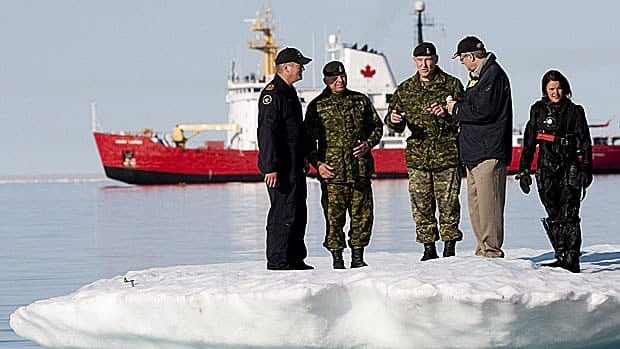 Prime Minister Stephen Harper, second from right, talks with Chief of the Defence Staff General Walter Natynczyk (centre) as they take part in a training exercise in Resolute, Nunavut on Aug. 25, 2010. The Canadian Coast Guard's medium icebreaker Henry Larsen is seen in Allen Bay. Canadian activity in the North, from searching for the Franklin expedition wreck to military manoeuvres, are about establishing sovereignty, experts say.