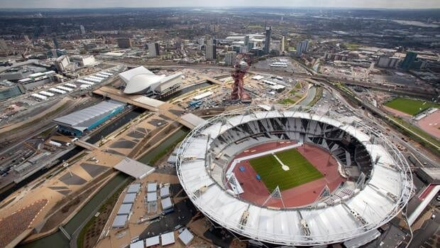 An aerial view of the Olympic Park shows the London 2012 Olympic Stadium, foreground and the Aquatics Center, the white building at left.