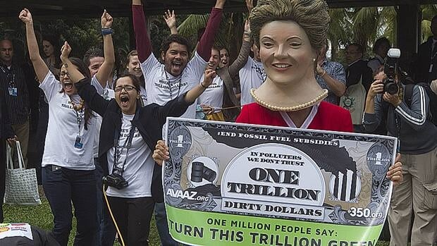 Environmental activists, one portraying Brazilian President Dilma Rousseff holding a banner symbolizing dirty money made from fossil fuel subsidies, shout slogans during a protest on the final day of the UN Conference on Sustainable Development, or Rio+20, in Rio de Janeiro, June 22.