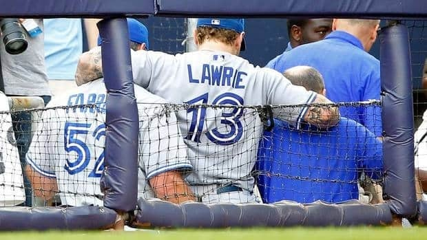 Brett Lawrie of the Toronto Blue Jays is helped to the locker room by a trianer and manager John Farrell after falling into the photographers box trying to catch a foul ball against the New York Yankees on Wednesday in New York City.