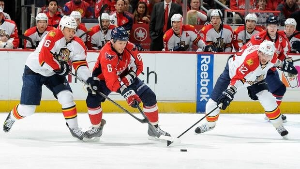 Dennis Wideman (6) of the Washington Capitals battles for the puck against Marco Sturm (16) and Tomas Kopecky (82_ of the Florida Panthers on Thursday.