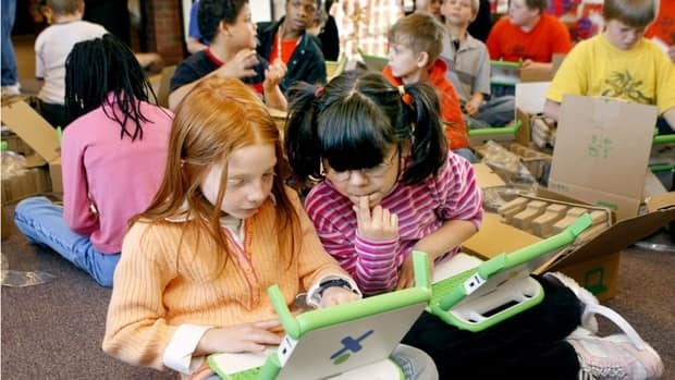 First-graders in an Illinois school help each other learn to use new computers in 2008. New research from the University of British Columbia has found that children who perform small acts of kindness tend to boost their own happiness, and that may help counteract bullying.