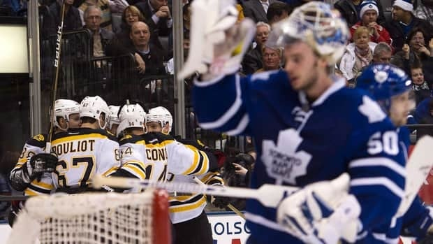 Toronto Maple Leafs goalie Jonas Gustavsson, right, looks away as the Boston Bruins celebrate their goal during the first period Tuesday.