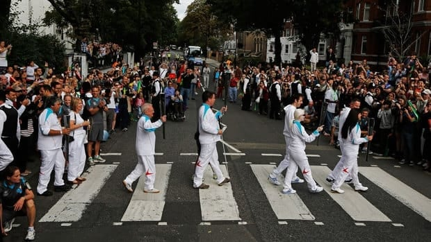 Torch bearers carry the Paralympic flame across the Abbey Road pedestrian crossing, near The Beatles former recording studio in London on Wednesday.