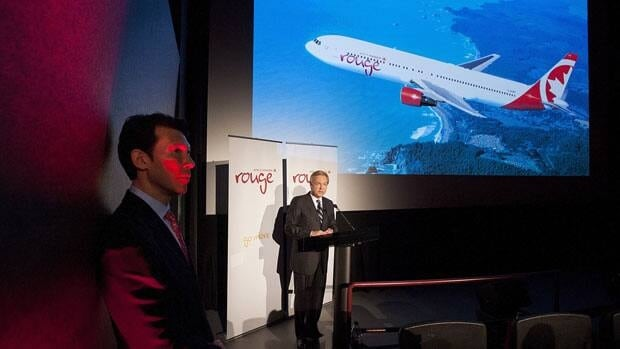 Michael Friisdahl, right, chief executive officer of Air Canada Leisure Group, unveils the new leisure airline Air Canada Rouge with executive vice-president Ben Smith, left, in Toronto on Tuesday.