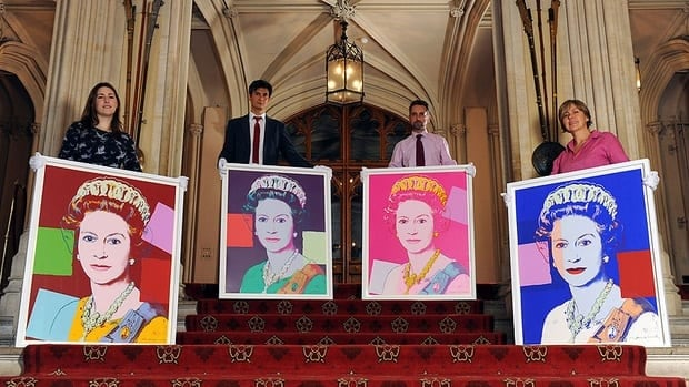 Exhibition curator Lauren Porter, left, and Royal Collection staff Allan Chinn, second left, Martin Clayton and Kate Stone stand with four Andy Warhol portraits of Queen Elizabeth II in Windsor Castle on Monday.