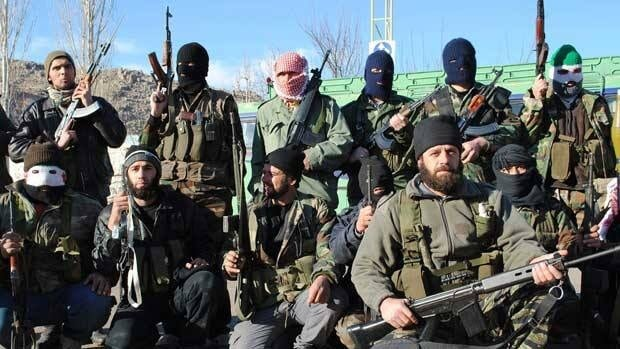 Syrian army defectors gather at the mountain resort town of Zabadani, Syria, near the Lebanese border, on Friday. At least 14 people were killed when multiple explosive devices struck a police truck transporting prisoners in a tense area of northwestern Syria on Saturday, the state-run news agency and an opposition group said.