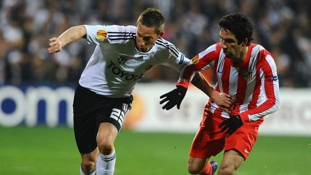Besiktas' Filip Holosko, left, vies with Atletico Madrid's Arda Turan during the UEFA Europa League Round of 16 match at Inonu Stadium in Istanbul, on March 15, 2012.