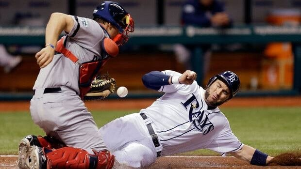 Tampa Bay Rays' Luke Scott, right, scores as Boston Red Sox catcher Ryan Lavarnway can't hang onto the ball in the fifth inning on Monday.