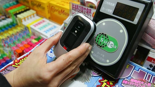 A mobile phone embedded with a computer chip is used to buy things at a kiosk by tapping it on a reading device at Tokyo's Shinjuku train station. Monday's CBA framework is a small step toward a similar system in Canada.