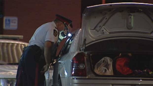 Police look at a car that was abandoned in front of the Northeast Health Centre after the driver dropped off two people with gunshot wounds and fled.