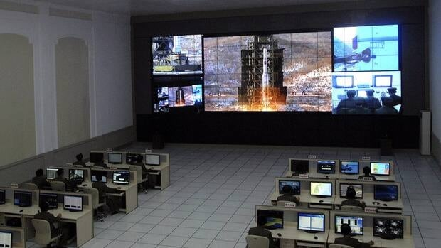 North Korean scientists work as a screen shows the Unha-3 (Milky Way 3) rocket being launched from a launch pad at the West Sea Satellite Launch Site, at the satellite control centre in Cholsan county, North Pyongan province in this picture released by the North's official KCNA news agency in Pyongyang Dec. 12.