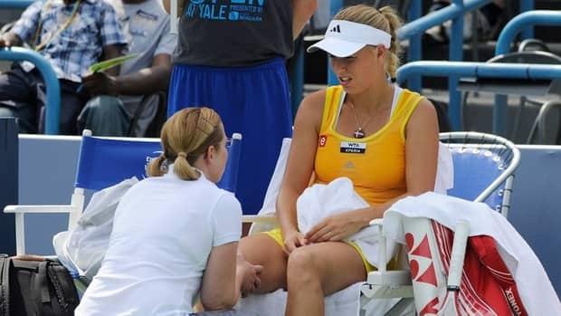 Caroline Wozniacki speaks with trainer before retiring from her semifinal match against Maria Kirilenko on Friday, Aug. 24, 2012.