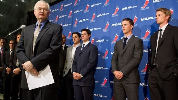 NHLPA executive director Donald Fehr, left, stands in front of players, including Pittsburgh Penguins superstar Sidney Crosby, back centre, as he addresses the media following an hour-long talk with NHL owners.