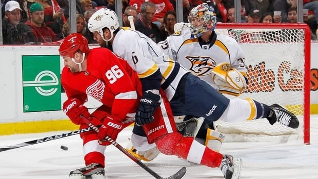 Tomas Holmstrom of the Detroit Red Wings, left, turns for the puck while being checked by Shea Weber of the Nashville Predators.