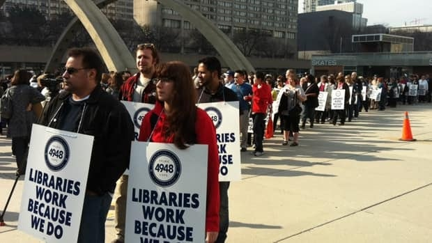 Toronto library workers picket in front of the City Hall branch on Monday morning.
