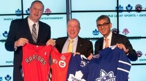 Bell Canada president and CEO George Cope, left, MLSE chairman Larry Tanenbaum, centre, and Rogers Communications president and CEO Nadir Mohamed pose with team jerseys at Friday's press conference in Toronto.