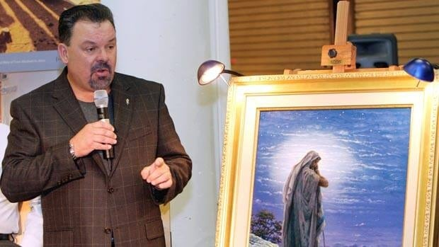 Artist Thomas Kinkade unveils his painting, Prayer For Peace, at the opening of the exhibit From Abraham to Jesus, on Sept. 15, 2006, in Atlanta.