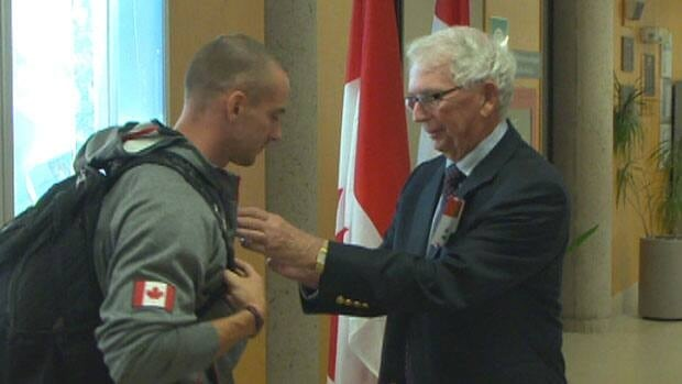 P.E.I. sprinter Jared Connaughton receives the Queen's Diamond Jubliee Medal from Lieutenant-Governor Frank Lewis.