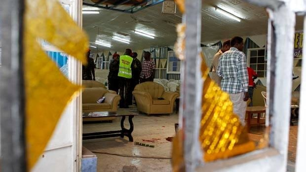 Detectives inspect the scene of an explosion inside a Nairobi church where at least one person was killed and a dozen wounded in a grenade attack.