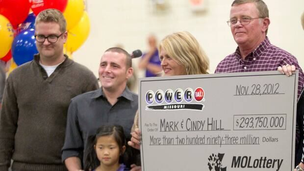 Mark and Cindy Hill hold a Powerball cheque with three of their four children, Jarod, left, Cody and six-year-old Jaiden in Dearborn, Mo., on Friday.
