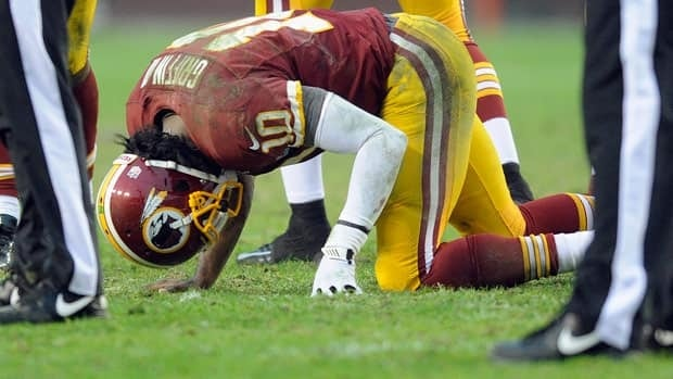 Washington Redskins quarterback Robert Griffin III kneels on the ground after his injury during the second half of an NFL football game against the Baltimore Ravens in Landover, Md., on Sunday.
