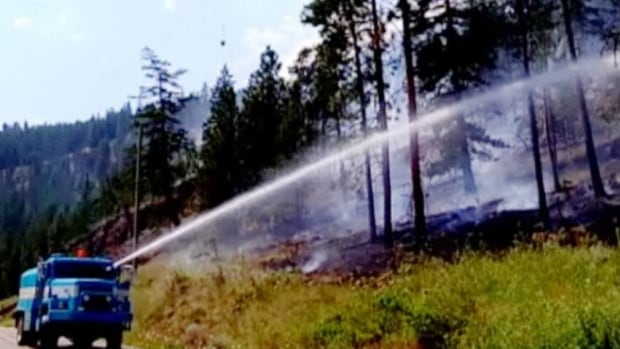 Crews spray water on a stubborn fire in Wilsons Landing in West Kelowna. B.C.'s Wildifire Management Branch said as of late Monday night the fire was 75 per cent contained.