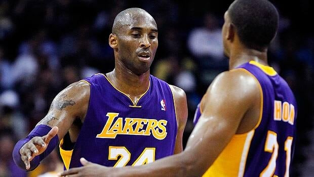 Los Angeles Lakers shooting guard Kobe Bryant is greeted by point guard Chris Duhon after setting the milesone Wednesday in New Orleans.