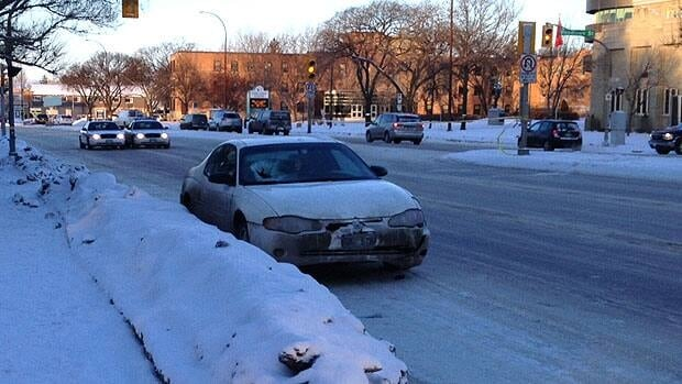A vehicle sits at the side of Portage Avenue, near Woodlawn Sreet, after a woman was struck.