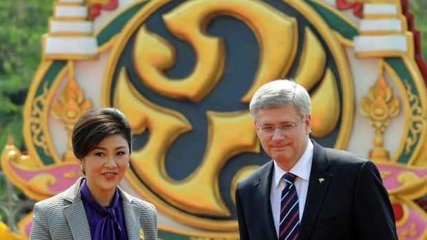 Prime Minister Stephen Harper is escorted by Yingluck Shinawatra, Prime Minister of Thailand, during an official visit to Bangkok. Harper announced support on Saturday for projects to fight human smuggling in Thailand.