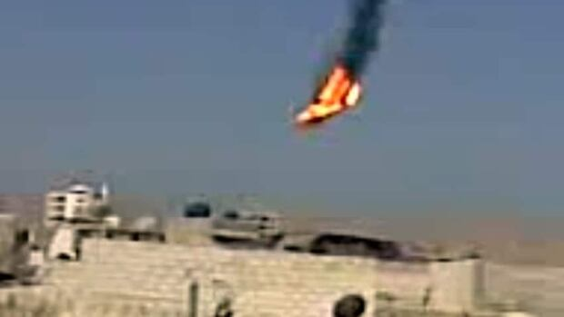 This citizen journalism image made from video provided by Shaam News Network SNN purports to show a Syrian military helicopter on fire and falling to the ground after it was apparently hit during fighting between government forces and rebels in the capital Damascus.