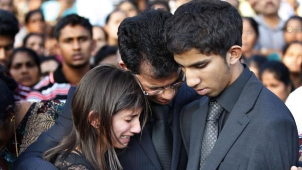 The husband of nurse Jacintha Saldanha Benedict Barboza, centre, holds his son Junal, right, and daughter Lisha during her funeral in her hometown Shirva, near Mangalore in southwest India on Monday. Saldanha was found hanging in her room days after she had been duped by a hoax call from an Australian radio station about the pregnant Duchess of Cambridge.