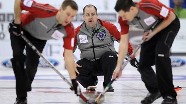 NWT/Yukon skip Jamie Koe, centre, watches his shot as second Brad Chorostkowski, left, and lead Robert Borden sweep at the Tim Hortons Brier in Saskatoon, Sask.